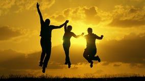 Familie die bij zonsondergang lopen en op het opheffen van hun handenwinnaars springen stock video