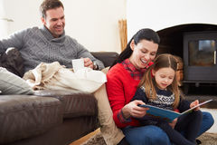 Familie die binnen en Boek ontspannen lezen stock foto