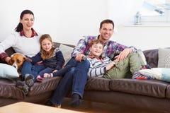 Familie die binnen op het Letten Televisie samen ontspannen royalty-vrije stock afbeeldingen