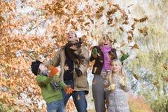 Familie die bladeren in de lucht werpt Stock Foto's
