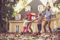 Familie die buiten spelen Het seizoen van de herfst Weg in dalingsbos Stock Foto's
