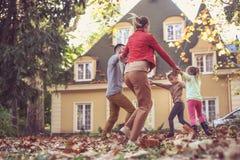 Familie die buiten spelen Het seizoen van de herfst Weg in dalingsbos In beweging Stock Foto