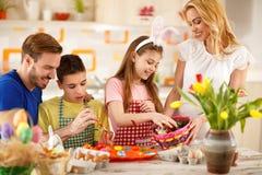 Familie, die bunte Eier malt und für Ostern sich vorbereitet Lizenzfreie Stockfotos