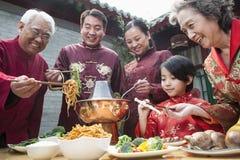 Familie, die chinesische Mahlzeit in der Kleidung des traditionellen Chinesen genießt Lizenzfreies Stockfoto