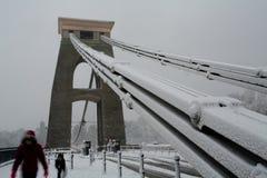 Familie, die Clifton Hängebrücke im Schnee kreuzt Stockfotografie