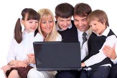 Familie die computer bekijkt Stock Foto's