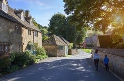 Familie, die in Cotswold-Dorf, England geht Lizenzfreies Stockbild