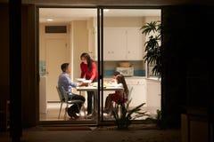 Familie, die das Abendessen angesehen von der Außenseite isst stockfoto