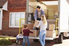 Familie, die das Bewegen in Kästen vom Abbau-LKW auspackt Lizenzfreies Stockfoto