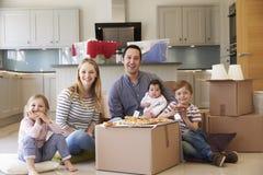 Familie, die das Bewegen in neues Haus mit Pizza feiert Stockfotos