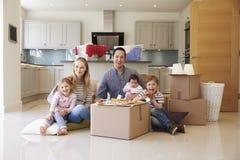 Familie, die das Bewegen in neues Haus mit Pizza feiert Stockfoto