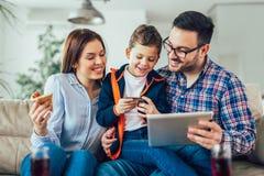 Familie, die das on-line-Einkaufen mit Tablette tut stockfotografie