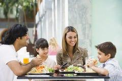 Familie, die das Mittagessen am Kaffee genießt Stockfotografie