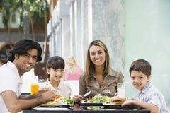 Familie, die das Mittagessen am Kaffee genießt Lizenzfreies Stockfoto