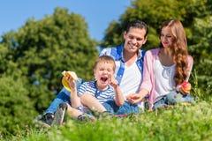 Familie, die das Picknick sitzt im Gras auf Wiese hat Stockfoto