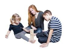 Familie, die das Spiel zusammen zu Hause lokalisiert auf weißem Hintergrund spielt Stockbilder