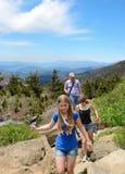 Familie die in de bergen wandelt Stock Foto's
