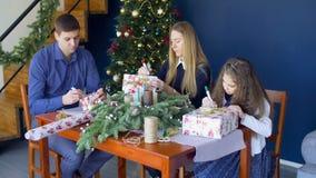Familie die de dozen van de Kerstmisgift op Kerstmisvooravond ondertekenen stock videobeelden