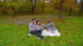 Familie die in de herfstpark Frieten eten, drinkend koffie op picknick stock video