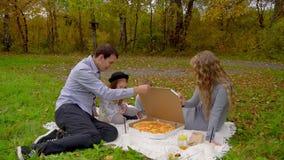 Familie die in de herfstpark pizza op het gazon eten stock videobeelden