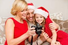 Familie die in de hoeden van de santahelper pictires bekijken Stock Foto