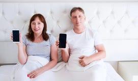Familie die in de slaapkamer liggen en mobiele telefoons houden stock afbeelding