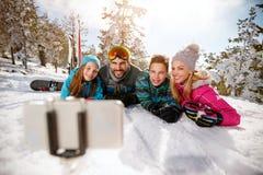 Familie die de winter van vakanties in bergen genieten en selfie maken Stock Foto's