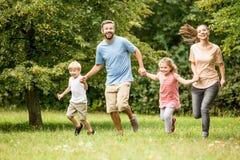 Familie die de zomer van activiteiten genieten bij park royalty-vrije stock afbeelding