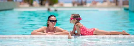Familie die de zomer van vakantie in luxe zwembad genieten royalty-vrije stock afbeeldingen