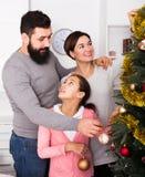Familie, die Dekorationen auf Weihnachtsbaum setzt Lizenzfreies Stockbild