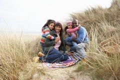 Familie, die in den Dünen auf Winter-Strand sitzt Lizenzfreies Stockfoto