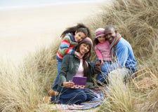 Familie, die in den Dünen genießen Picknick auf Winter sitzt Stockfotografie