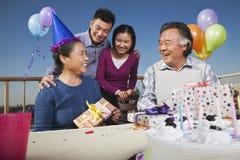 Familie, die den Geburtstag der Mama, öffnende Geschenke feiert und Spaß hat Stockfotos