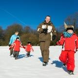 Familie, die in den Schnee läuft Stockbild