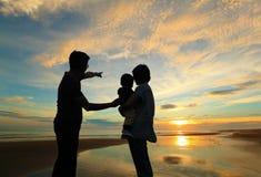 Familie, die den Sonnenaufgang auf dem Strand aufpasst Stockfotografie