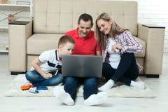 Familie, die den Spaß chating ist auf Internet mit Laptop hat Familie, die hat Stockfoto