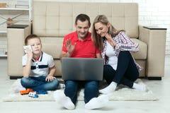 Familie, die den Spaß chating ist auf Internet mit Laptop hat Familie, die hat Stockfotos