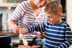 Familie, die in der Küche kocht Lizenzfreie Stockfotos