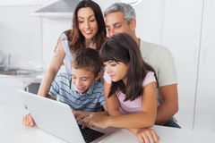 Familie, die in der Küche unter Verwendung ihres Laptops sitzt Stockfoto