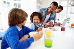 Familie, die in der Küche vor Schule frühstückt Stockbild