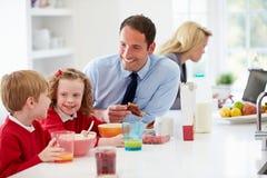 Familie, die in der Küche vor Schule und Arbeit frühstückt Lizenzfreie Stockfotos