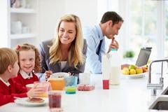 Familie, die in der Küche vor Schule und Arbeit frühstückt Stockbilder