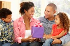 Familie, die der Mutter Geschenk gibt stockfotos