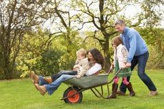 Familie, die in der Schubkarre spielt Lizenzfreie Stockfotos