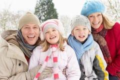 Familie, die in der Snowy-Landschaft sitzt Stockbilder