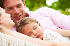 Familie, die in der Strand-Hängematte mit schlafender Tochter sich entspannt Stockbild