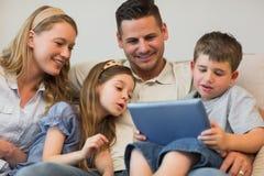 Familie die digitale tablet samen op bank gebruiken Royalty-vrije Stock Afbeelding
