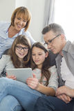 Familie die digitale tablet samen in woonkamer gebruiken Stock Afbeeldingen