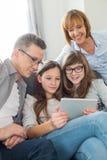 Familie die digitale tablet samen in woonkamer gebruiken Stock Foto