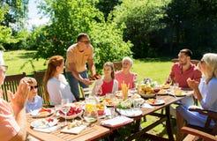 Familie die diner of barbecue hebben bij de zomertuin stock afbeelding
